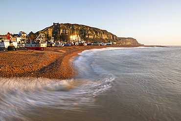 Fishing boats on beach at The Stade with breaking waves and East Hill behind at sunrise, Hastings, East Sussex, England, United Kingdom, Europe