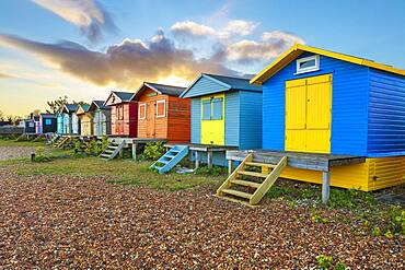 Colourful beach huts on shingle beach at sunrise, Whitstable, Kent, England, United Kingdom, Europe