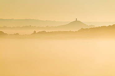 Glastonbury Tor and surrounding hills rising above early morning mist, Glastonbury, Somerset, England, United Kingdom, Europe