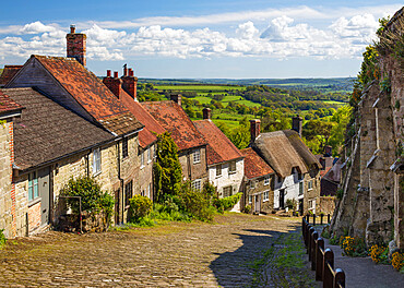 Gold Hill cobbled lane lined with cottages and views over countryside, Shaftesbury, Dorset, England, United Kingdom, Europe