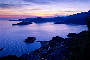 Sunset over Sveti Stefan and bay, Sveti Stefan, The Budva Riviera, Montenegro, Europe