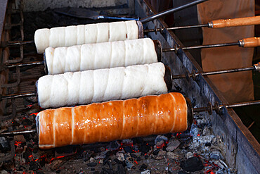 Kurtoskalacs (chimney cake) (stove cake) cooking over coals, Budapest, Hungary, Europe