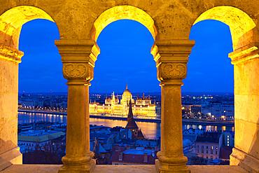 Parliament (Orszaghaz) through arches of Fishermen's Bastion (Halaszbastya) at dusk, UNESCO World Heritage Site, Budapest, Hungary, Europe
