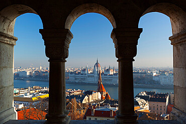 Parliament (Orszaghaz) and River Danube through arches of Fishermen's Bastion (Halaszbastya), UNESCO World Heritage Site, Buda, Budapest, Hungary, Europe