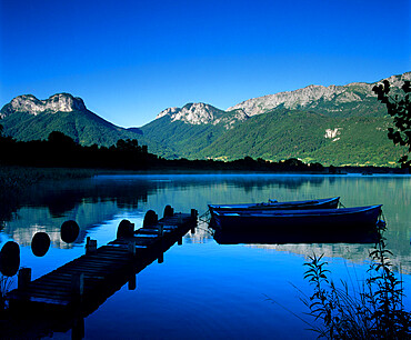Silhouette of pier and rowing boats, Lake Annecy, Rhone Alpes, France, Europe