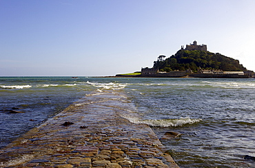 The old stone causeway leading to St. Michaels Mount submerged by the incoming tide cutting it off from Marazion, Cornwall, England, United Kingdom, Europe