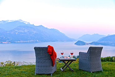 Armchairs and red wine with views of Lake Como at sunset, Lombardy, Italian Lakes, Italy, Europe
