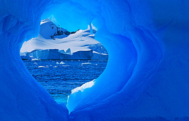 Heartshaped hole in an Antarctic blue iceberg. Pléneau Island, Antarctica