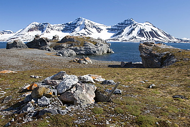 A view of the towering cliff and glacier in Hornsund (Horn Sound) on the southwestern side of Spitsbergen Island in the Svalbard Archipelago, Barents Sea, Norway. Shown here is a trappers gravesite.