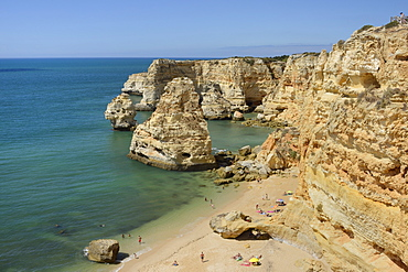 Overview of tourists on beach, sandstone cliffs and seastacks at Praia da Marinha, near Carvoeiro, Algarve, Portugal, Europe