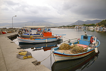 Moored fishing boats in Apothika village harbour, with clouds over mountains in the background, Lesbos (Lesvos), Greek Islands, Greece, Europe