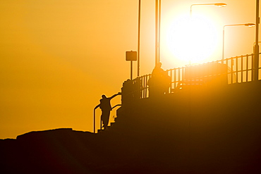 Oban esplanade with setting sun behind lamp posts and people. Oban, Argyll, Scotland, UK