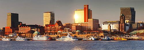 View from Elbe River to St. Pauli Landungsbruecken pier and skyscraper Tanzende Tuerme at sunset, St. Pauli, Hamburg, Europe