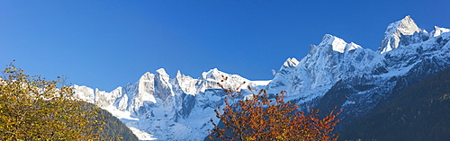 Panorama of the snowy peaks framed by colorful trees, Soglio, Bregaglia Valley, Canton of Graubunden, Switzerland, Europe