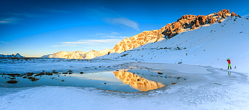 Panorama of Lake, Piz Umbrail at dawn with photographer in action framed by snow, Braulio Valley, Valtellina, Lombardy, Italy, Europe