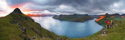 Panoramic of hikers on cliffs looking to the fjords, Funningur, Eysturoy island, Faroe Islands, Denmark, Europe