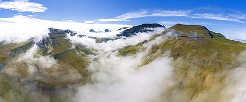 Panoramic aerial view of clouds on mountain peaks, Gjogv, Eysturoy island, Faroe Islands, Denmark, Europe