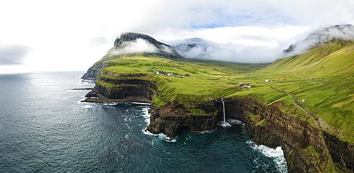 Aerial panoramic of waterfall and cliffs, Gasadalur, Vagar island, Faroe Islands, Denmark, Europe