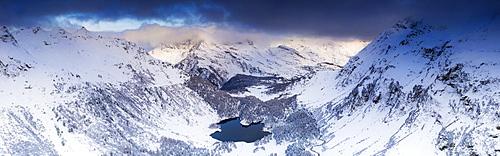 Aerial panoramic of Lake Cavloc and snowy woods, Bregaglia Valley, Engadine, canton of Graubunden, Switzerland, Europe