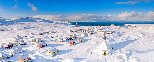 Aerial view of traditional houses and church in the small village of Hasvik after a snowfall, Troms og Finnmark, Northern Norway, Scandinavia, Europe