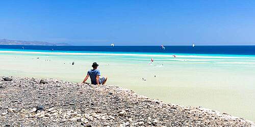 Man sitting on rocks looking at the kitesurfers in the clear sea, Sotavento beach, Jandia, Fuerteventura, Canary Islands, Spain