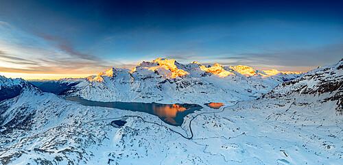 Winding road of Bernina pass in the winter landscape nearby the frozen Lago Bianco at sunrise, Graubunden, Engadin, Switzerland