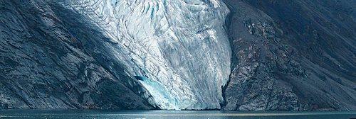 Panorama imag of glacier fingers coming down to seashore.