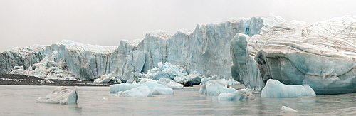 Panorama image of glacier face with zodiac crusing among the icebergs, Nunavut and Northwest Territories, Canada, North America