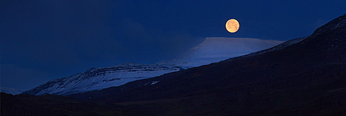 Panorama of full moon above snow covered mountains, Iceland, Polar Regions