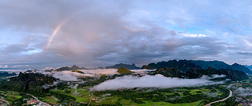 A panorama of a rainbow as dawn breaks over the mountains of Vang Vieng, Laos, Indochina, Southeast Asia, Asia