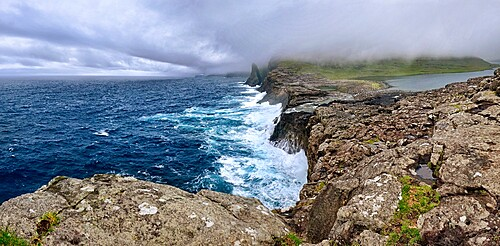 Panorama of Bosdalafossur, a waterfall that flows from the lake directly in the ocean, Faroe Islands, Denmark, Europe