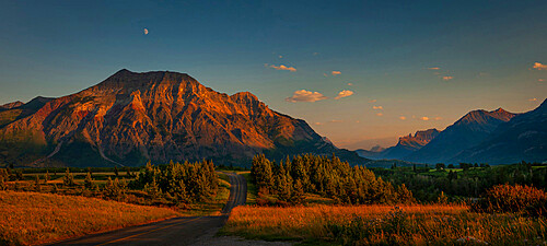 Waterton-Glacier mountains at sunset, UNESCO World Heritage Biosphere site with a lone road leading off into the distance, Alberta, Canada, North America