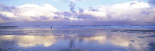 Beach at Embleton Bay with lone walker, dramatic clouds and reflections in wet sand, near Alnwick, Northumberland, England, United Kingdom, Europe
