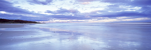 Beach at Alnmouth at dusk with dramatic clouds reflecting in wet sand at low tide, near Alnwick, Northumberland, England, United Kingdom, Europe