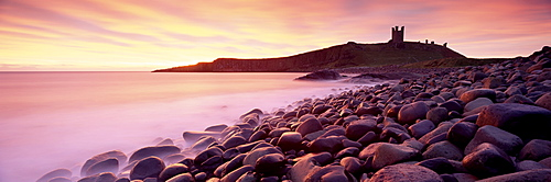 An imposing silhouette of Dunstanburgh Castle against a magnificent sky at sunrise with a beach of basalt boulders in the foreground, Embleton Bay, near Alnwick, Northumberland, England, United Kingdom, Europe