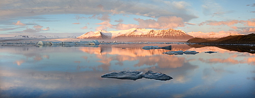 Panoramic view across the calm water of Jokulsarlon glacial lagoon towards snow-capped mountains and icebergs bathed in late afternoon light in winter, at the head of the Breidamerkurjokull Glacier on the edge of the Vatnajokull National Park, South Iceland, Iceland, Polar Regions