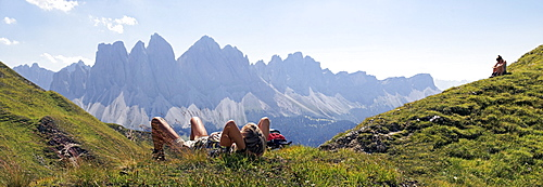 Hikers relaxing and enjoying the view of the Geisler Group, Aferer Geisler Mountains, Villnoesstal valley, province of Bolzano-Bozen, Italy, Europe