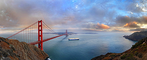 Panoramic view of the Golden Gate Bridge at sunset with a rainbow and storm clouds, San Francisco, California, United States, North America