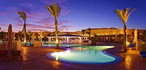 Swimming pool with palm trees at sunset, Hilton Nubian Resort, Al Qusair, Marsa Alam, Egypt, Africa