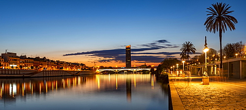 View over the river Rio Guadalquivir with illuminated bridge Puente de Triana and promenade, in the back skyscraper Torre Sevilla, sunset, blue hour, Sevilla, Andalusia, Spain, Europe