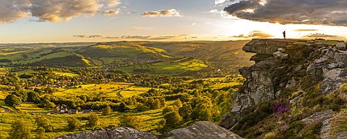 View of lone piper at at sunset on Curbar Edge, Curbar, Hope Valley, Peak District National Park, Derbyshire, England, United Kingdom, Europe