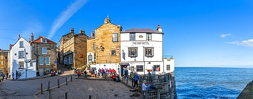 View of white washed Bay Hotel and visitors at harbour in Robin Hood's Bay, North Yorkshire, England, United Kingdom, Europe