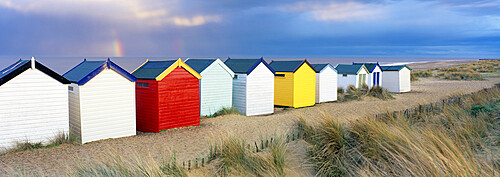 Beach huts and sand dunes with rainbow in evening light, Southwold, Suffolk, England, United Kingdom, Europe