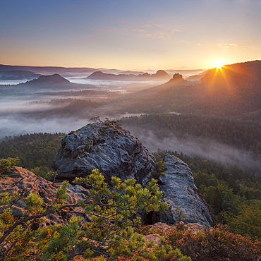 View from Gleitmannshorn over the small Zschand with fog at sunrise with rocks in foreground, Kleiner Winterberg, National Park Saxon Switzerland, Saxony, Germany