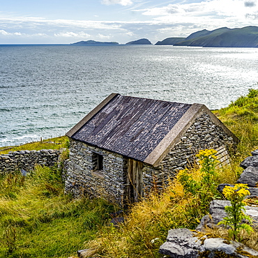 A small stone house along the coastline of County Kerry with cliffs and mountains in the distance, Ballyferriter, County Kerry, Ireland