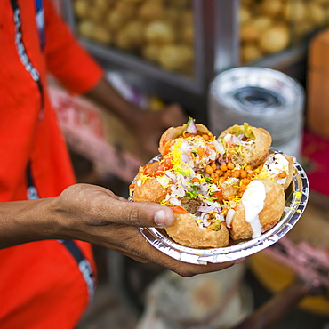 A hand holding a foil plate with a serving of traditional Indian food, Jaipur, Rajasthan, India