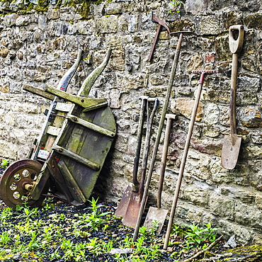 Old garden tools leaning up against a weathered stone wall, Open Air Museum, England