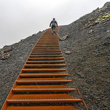 Climbing metal steps up volcanic rock in the rain; Snaefellsbaer, Western Region, Iceland