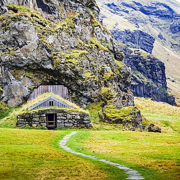Barn built into a rocky mountainside, now overgrown with grass; Rangarping eystra, Southern Region, Iceland
