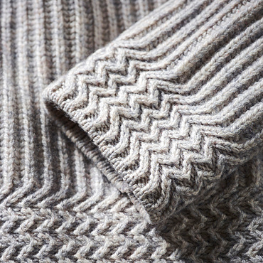 Extreme close-up of the cuff of a grey knit sweater; Studio